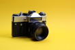 canvas print picture - Retro camera. Old film camera on a yellow background