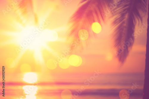 Foto auf Leinwand Koralle Blur beautiful nature green palm leaf on tropical beach with bokeh sun light wave abstract background.
