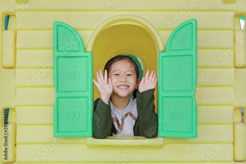 Fotografia, Obraz Happy little Asian child girl playing with window toy playhouse in playground