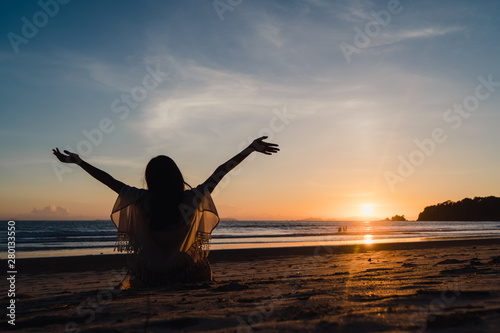 Foto auf Leinwand Grau Young Asian woman watching sunset near beach, beautiful female happy relax enjoy moment when sunset in evening. Lifestyle woman travel on beach concept.