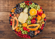 Fresh raw organic summer berries and exotic fruits in round large tray on wooden kitchen background. Papaya, grapes, nectarine, orange, raspberry, kiwi, strawberry, lychees, cherry.