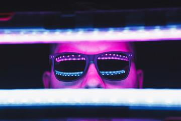 Neon light studio close-up portrait of serious man model with sunglasses