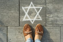 Female Feet With Abstract Image Of Six Pointed Star, Written On Grey Sidewalk
