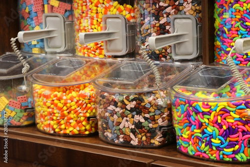 Bright colors candy background. Assorted bulks of colorful candies in plastic boxes at the candy shop close up.