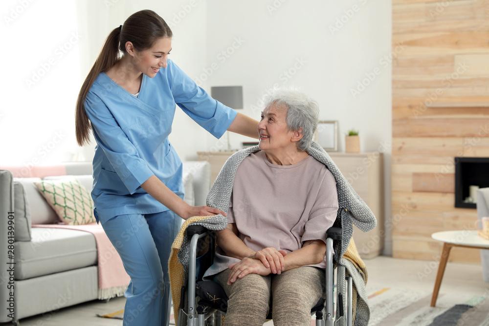 Fototapeta Nurse covering elderly woman in wheelchair with blanket indoors. Assisting senior people