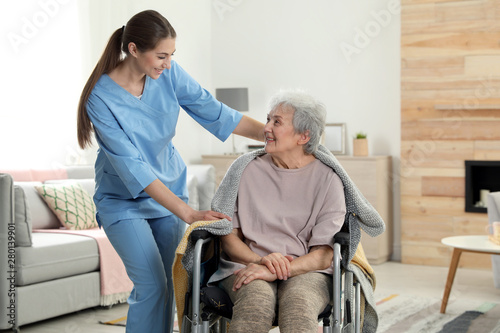 Obraz Nurse covering elderly woman in wheelchair with blanket indoors. Assisting senior people - fototapety do salonu