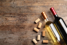 Flat Lay Composition With Bottles Of Wine And Corks On Wooden Table. Space For Text