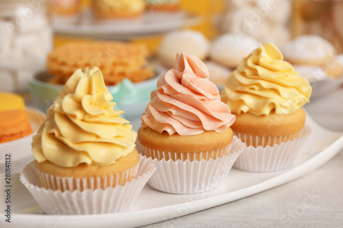 Photo  Tasty cupcakes and other sweets on table. Candy bar, closeup view