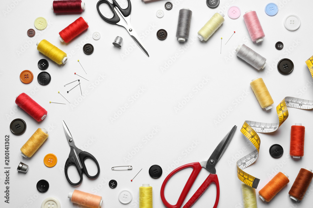 Fototapeta Frame made of scissors and other sewing accessories on white background, top view. Space for text