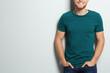 Leinwandbild Motiv Young man wearing blank t-shirt on light background, closeup. Mockup for design