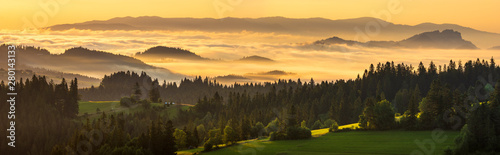 Fototapeta A beautiful mountain view. Mountains and green hills emerging from the morning mists illuminated by the rising sun. A view from the top of the Czarna Góra mountain in Poland obraz