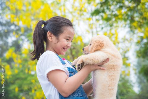 Young asian girl holding a little golden retriever dog in park Poster Mural XXL