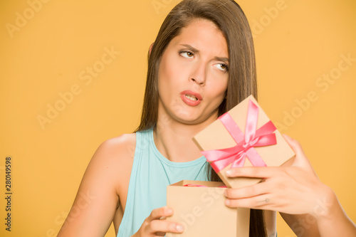 Young disappointed woman opening a present box on yellow background Tablou Canvas