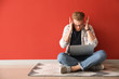 canvas print picture - Stressed young man with laptop sitting near color wall