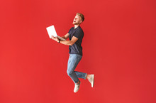 Jumping Young Man With Laptop On Color Background