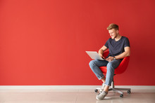 Handsome Young Man With Laptop Sitting On Chair Near Color Wall