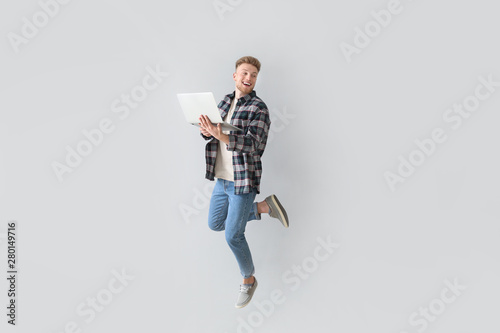 Fotografia Jumping young man with laptop on light background