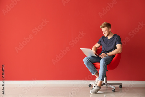 Handsome young man with laptop sitting on chair near color wall - 280149761