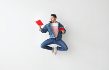 Jumping Young Man With Books O...