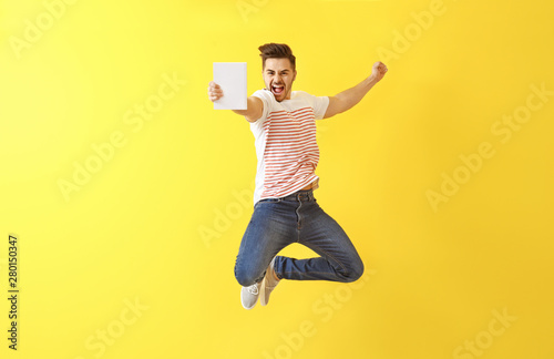 Jumping young man with book on color background Wallpaper Mural