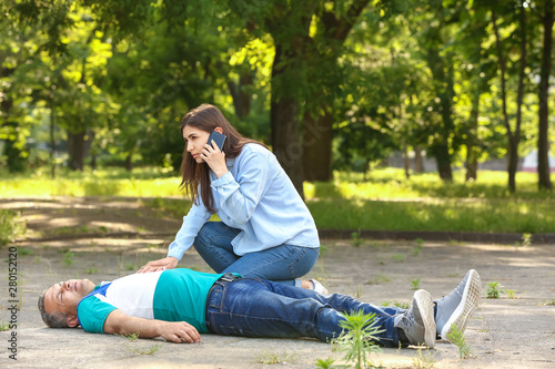Obraz Female passer-by calling an ambulance for unconscious mature man outdoors - fototapety do salonu