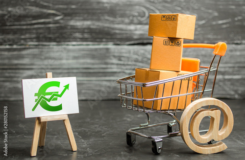A shopping cart with boxes symbolizing internet trading and a stand with a green Euro up arrow Canvas-taulu