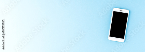 Mobile phone on blue desktop with copyspace. Banner Fototapeta