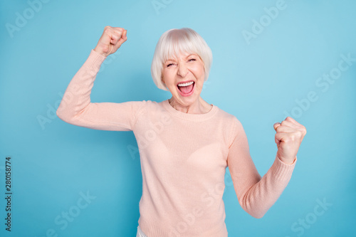 Fotografía  Portrait of cheerful lady shouting yeah raising fists wearing pastel sweater iso