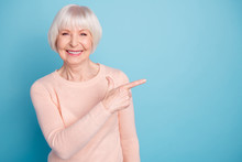 Portrait Of Pretty Lady Pointing At Copy Space Smiling Wearing Pastel Jumper Isolated Over Blue Background