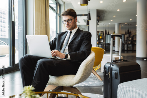 Fototapeta Portrait of caucasian young businessman sitting on armchair with laptop computer and suitcase in hotel hall obraz