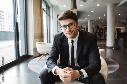 Photo of young businessman wearing eyeglasses sitiing on armchair in hotel lobby