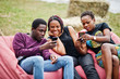 canvas print picture - Three african american friends chill, sitting on poufs and using their phones outdoor.