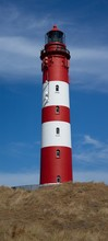 Beautiful Vertical Shot Of A Red And White Striped Lighthouse Tower At The Beach