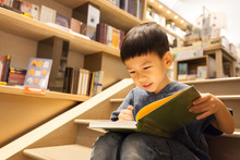 Portrait Of Adorable Little Preschool Asian Boy Sitting On Stairs, Reading Book In Library With Fun And Full Concentration. Child's Brain Development, Learn To Read, Cognitive Skills Concept.