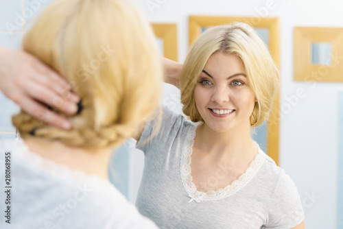Woman in bathroom styling hair