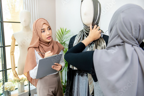 Cuadros en Lienzo  Muslim woman designer working with colleague measuring size of the dress