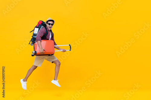 Foto Handsome Indian tourist man with backpack holding baggage and jumping