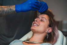 Young Woman Getting Pierced Between Her Eyes. Man Showing A Process Of Piercing With Steril Medical Equipment And Latex Gloves. Body Piercing Procedure