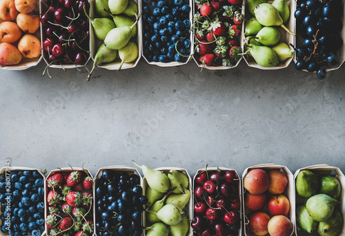 Summer fruit and berry variety. Flat-lay of ripe strawberries, cherries, grapes, blueberries, pears, apricots, figs in wooden eco-friendly boxes over grey background, top view, copy space