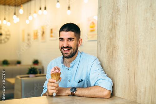 Fototapeta man eating ice cream in cone in cafe obraz