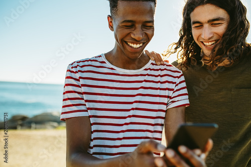 Obraz Two friends using a smart phone outdoors - fototapety do salonu