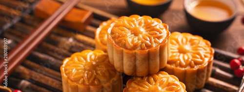 Moon cake Mooncake table setting - Round shaped Chinese traditional pastry with tea cups on wooden background, Mid-Autumn Festival concept, close up Wallpaper Mural