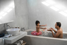 Little Girl With Her Father Playing Water On The Bathtub When Take A Bath Together