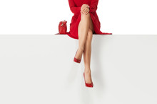 Beautiful Legs Woman Wearing Red Dress And High Heels Shoes Sitting On White Bench. Copyspace.