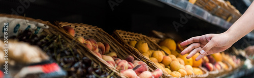 panoramic shot of young woman near fruits in supermarket