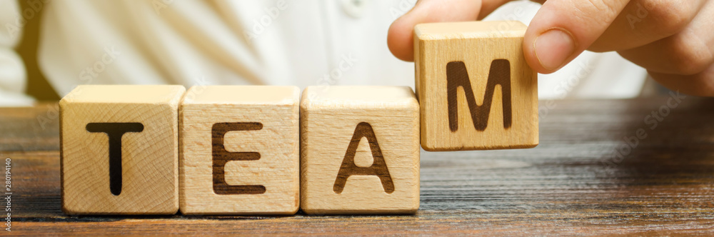 Fototapety, obrazy: Businessman holds wooden blocks with the word Team. Team management concept. Teamwork. Hiring. Recruitment staff. Work in cooperation. Leadership skills. Analysis and analytics business process