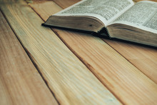 Close Up Open Bible Book On A Wooden Table Background.
