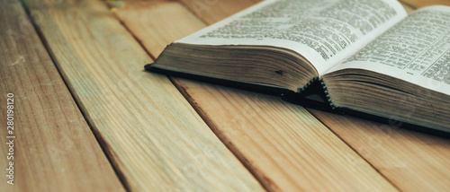 Close up open Bible book on a wooden table background. Wallpaper Mural