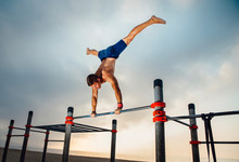 Fitness, Sport, Training, Calisthenics And Lifestyle Concept - Young Man Exercising Handstand On Bar Outdoors