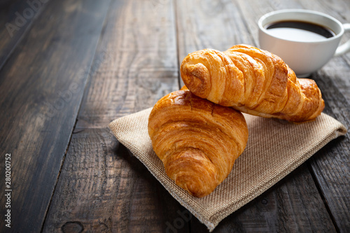 Cuadros en Lienzo croissants and coffee on old wooden table.